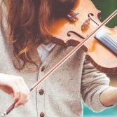 woman-in-gray-cardigan-playing-a-violin-during-daytime-111287